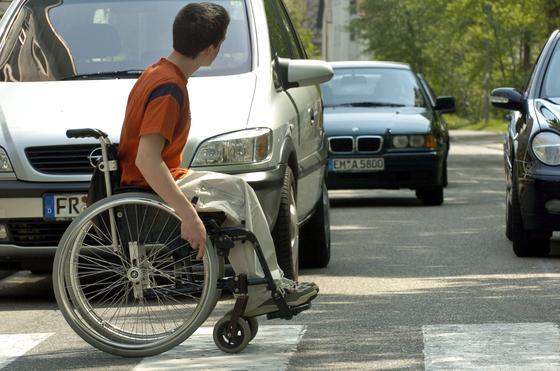 """Rollstuhlfahrer überquert einen Zebrastreifen: Fortbewegung ist für Rollstuhlfahrer oft beschwerlich. Erst recht, wenn Hindernisse hinzu kommen. Informatikstudenten der Hochschule Darmstadt habenjetzt das neue Orientierungssystem """"Wheel-Guide"""" für Smartphones entwickelt. Mit dessen Hilfe finden sich Behinderte insbesondere in einer unbekannten Gegend besser zurecht. Die App informiert über Hindernisse auf dem Weg, die nicht bewältigt werden können und bietet Alternativ-Routen an."""