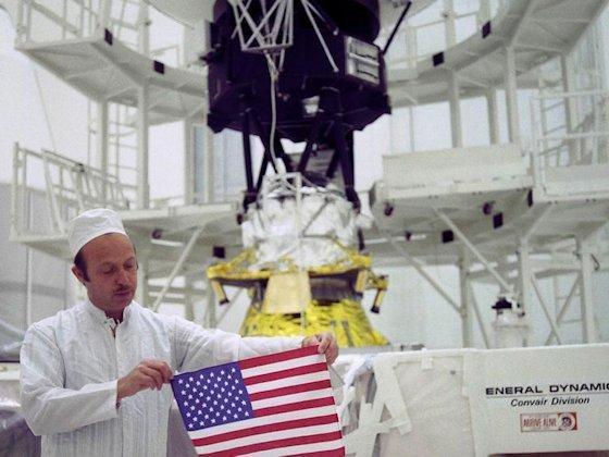Grüße in 60 Sprachen, verewigt auf einer goldenen Datenplatte, sowie natürlich die amerikanische Flagge gehörten zu Erstausstattung von Voyager, die Projektleiter John Casani 1977 stolz präsentierte. Im Hintergrund: Voyager 2.