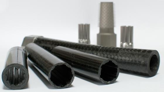 Antriebswellen mit unterschiedlich geformtem Innenquerschnitt. Im Hintergrund sind unterschiedliche Naben aus Stahl zu sehen.