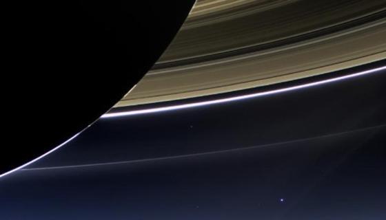 """Der kleine helle Fleck unter den Ringen des Saturn ist die Erde. Die Raumsonde """"Cassini"""" befand sich im Schatten des Saturn, als sie die Erde fotografierte."""
