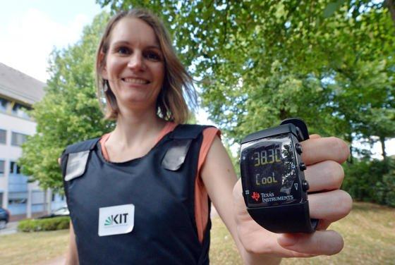 Kristina Schaaff, Doktorandin beim Institut für Technik der Informationsverarbeitung (ITIV) am Karlsruher Institut für Technologie (KIT), zeigt, dass die Klimajacke des KIT funktioniert. Mit der Uhr kann sie die Temperatur steuern. Die Jacke verschafft mit Hilfe von Ventilatoren Kühlung an heißen Sommertagen.