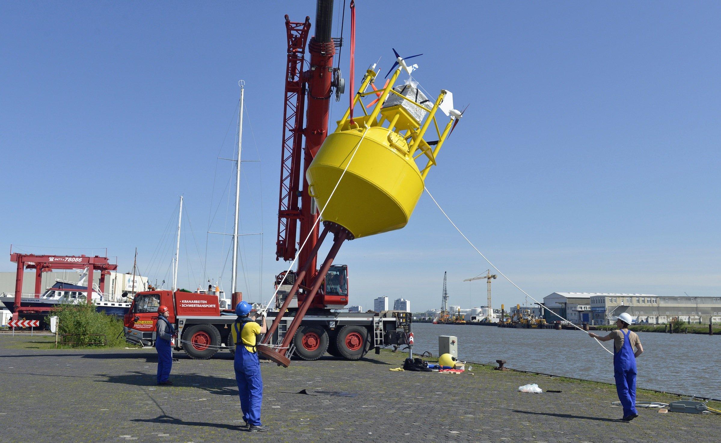 Mitarbeiter des Fraunhofer IWES richten in Bremerhaven die Boje an der Kaikante auf und setzen das Messgerät anschließend sicher ins Hafenbecken. Von Bremerhaven aus startete die Boje ihre Reise in Richtung des ersten deutschen Offshore-Windparks Alpha Ventus in der Nordsee.