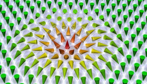 Ein magnetisches Skyrmion in einer hexagonalen Anordnung von Atomen: Die Kegel repräsentieren die magnetischen Spins.Sie zeigen im Zentrum des Skyrmions nach oben, außerhalb davon nach unten.