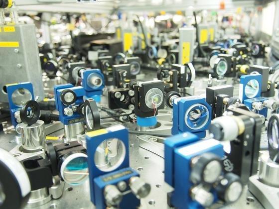Optischer Aufbau des Teleportationsexperiments an der Universität Tokio: Laserquellen und nichtlineare optische Prozesse liefern das Quantenbit und die notwendige Verschränkung. Spiegel und Strahlteiler ermöglichen eine komplette Teleportation.