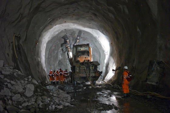 """Ingenieure betrachten am 9. September 2010 während einer """"sicherheitsorientierten Prüfung SIOP"""" auf der Baustelle des Teilabschnitts """"Sedrun"""" im Gotthard-Basistunnel bei Sedrun im Kanton Graubünden die rohe Tunnelwand."""
