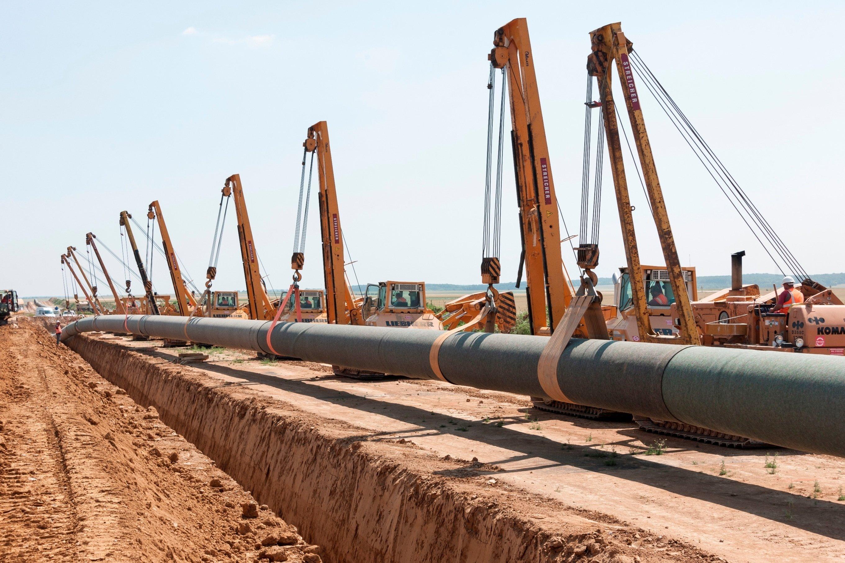 Neun Seitenbaumraupen senken die Pipeline in den Rohrgraben ab. Bei Unterquerungen von Straßen oder Flüssen werden auch grabenlose Verfahren wie das Microtunneling oder Direct Pipe angewandt.