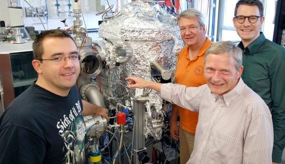 """Mit einer """"Sputter-Anlage"""" stellen (v.l.) Dr. Timo Kuschel, Prof. Dr. Andreas Hütten, Prof. Dr. Günter Reiss und Dr. Andy Thomas ihre Nano-Magnetschichten her. Das künftige Spinelektronik-Zentrum wird mit einer neuen, noch genaueren Sputter-Anlage ausgestattet."""