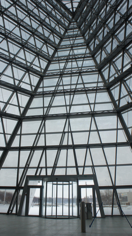 Die Eingangshalle von Innen: Das von dieser Seite schwarze Polyestergewebe erlaubt den freien Blick nach draußen. Installiert wurden die puzzleförmig angeordneten Glasscheiben auf dem Stahlgerüst mit Hilfe eines Pfosten-Riegel-Systems.