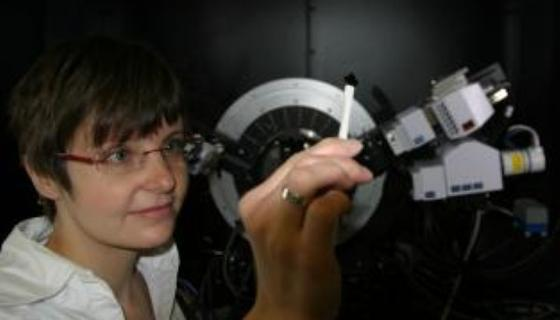 Forscherin Juliane Hanzig betrachtet im Labor ein dünnes Plättchen Strontiumtitanat.