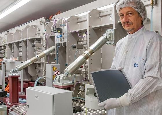 ZSW-Mitarbeiter Friedrich Kessler mit dem neuen flexiblen Dünnschicht-Solarmodul auf emailliertem Stahlsubstrat.