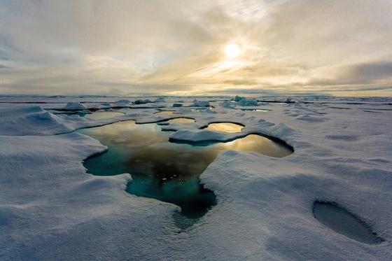 Schmelzwassertümpel auf dem arktischen Meereis. Deutlich ist der Tümpel als dunklerer Fleck auf der weißen Oberfläche zu erkennen.
