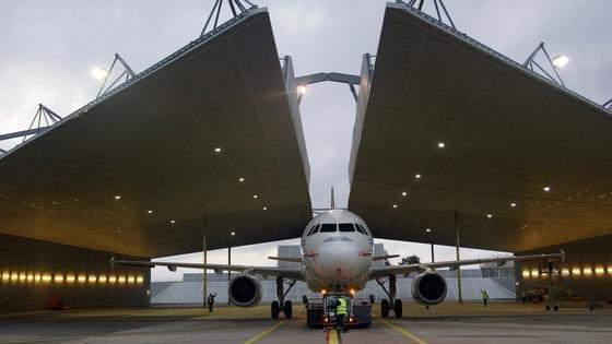 Rund um das DLR-Testflugzeug, ein Airbus A320, schließt sich die Lärmschutzhalle auf dem Hamburger Flughafen: Die Anwohner sollen von den Versuchen zum Fluglärm nicht belästigt werden. In der Halle untersuchen Ingenieure, wie und wo genau im Triebwerk der Lärm entsteht.