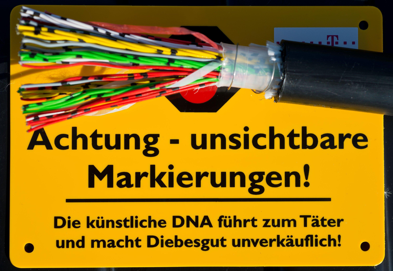 Warnschild der Deutschen Telekom: Mit einemaufgeschnittenen Freileitungs-Telefonkabel und dem Hinweis auf den Einsatz von künstlicher DNA will das Unternehmen Kupferdiebe abschrecken.