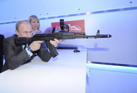 Russlands Präsident mit einem Sturmgewehr vom Typ AK-74 (AutomatKalaschnikow 74) im Anschlag. Putin treibt den Umbau des finanziell angeschlagenen Herstellers des berühmten Sturmgewehrs Kalaschnikow in ein modernes Unternehmen voran.