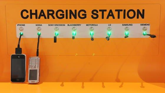 Ladestation für verschiedene Handys im CCD Congress Center Düsseldorf: Trotz einer Selbstverpflichtung sind Ladegeräte selbst mit gleichem Stecker so unterschiedlich, dass man in der Regel nur ein Gerät damit aufladen kann. Jetzt hat die EU einen neuen Vorstoß für einheitliche Netzteile gestartet.
