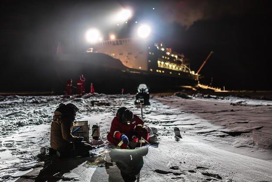 Die Forscher Steffi Arndt (l.) und Stephan Paul (r.) untersuchen die Eigenschaften des antarktischen Schnees im Scheinwerferlicht des deutschen Forschungsschiffes Polarstern.