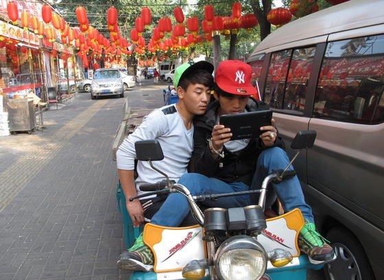 Zwei junge Chinesen mit Tablet auf dem Motorrad: Am Dienstag ist weltweiter Tablet-Day. Apple stellt seine neuen iPads vor, Microsoft-Tochter Nokia seine ersten Windows-Tablets und Microsoft seine Surface-Geräte. Damit dürfte sich die Konkurrenz auf dem Tablet-Markt weiter verschärfen.