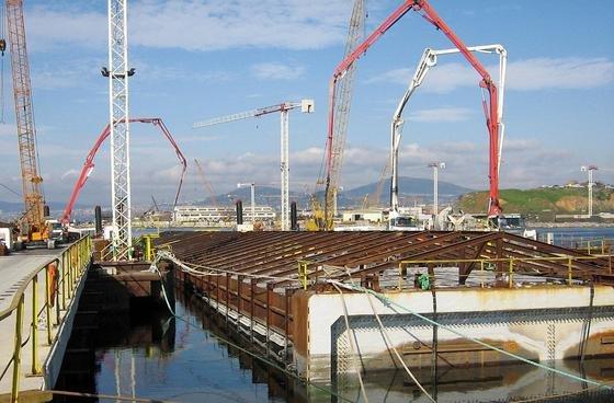 Riesige Betontröge, jeweils 30 000 Tonnen schwer, wurden an Seilen herabgelassen und unter dem Meeresgrund verankert.