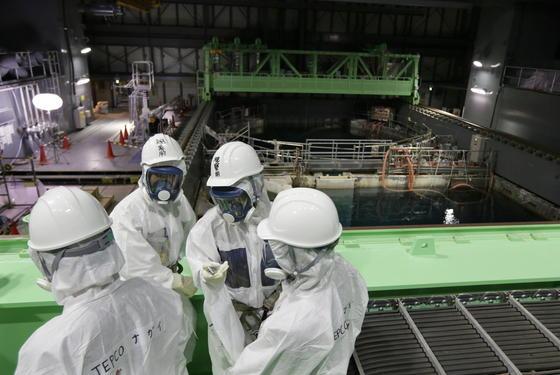Ingenieure vor dem Abklingbecken für Brennstäbe im Reaktor 4 des Atomkraftwerkes Fukushima: Die Bergung der 1300 Brennelemente wurde wegen technischer Probleme verschoben.