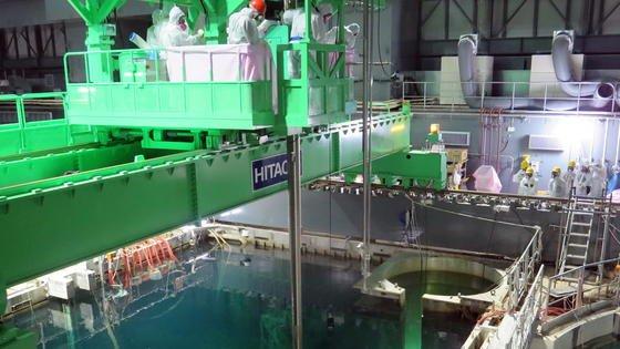 Reaktor 4 des havarierten AKW Fukushima: Mit einem Greifroboter laden Mitarbeiter seit heute Brennstäbe unter Wasser in Container. Dabei ist Vorsicht gefragt. Denn im Becken liegen tausende Trümmerteile.