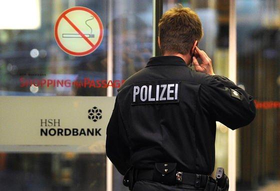 Ein Polizist geht am 19. November 2013 in Hamburg in ein Gebäude der HSH Nordbank. Die Geschäftsräume der Bank wurden wegen des Verdachts der Geldwäsche durchsucht.