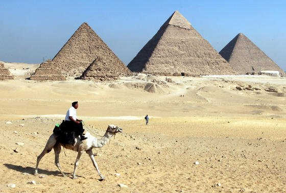 Ein ägyptischer Polizist auf einem Kamel reitet vor den Pyramiden von Gizeh. Aus einerKammer der Cheops-Pyramide habendeutsche Amateur-Archäologen ohne Genehmigung Farbe von der Wand gekratzt. Das ägyptische Ministerium für Altertümer will sie deshalb international zur Fahndung ausschreiben.