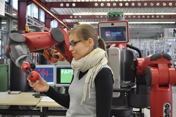 Der kooperative Forschungsroboter Baxter überreicht behutsam einen Apfel.Die Universität Erlangen-Nürnberg ist die erste in Deutschland, die die amerikanische Erfindung in ihre Forschungen integrieren kann.