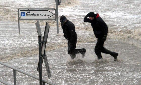 """Passanten laufen am 5. Dezember 2013 über den überfluteten Fähranleger in Dagebüll (Schleswig-Holstein) an der Nordsee. Das Orkantief """"Xaver"""" hat den Norden mit voller Wucht erreicht."""