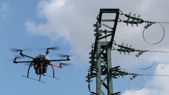 Die zwei Kilogramm schwere Drohne untersucht Strommasten aus nächster Nähe mit Kameras, Infrarot- und Ultraschallsensoren. Ist derzeit noch die Fernsteuerung vom Boden notwendig, soll der ein Meter große Multikopter in naher Zukunft selbstständig zum Einsatzort fliegen und autonom arbeiten.