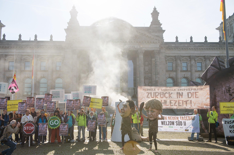 Aktivisten protestieren am 27. Juni 2014 in Berlin gegen die Verabschiedung des Erneuerbare-Energien-Gesetzes durch den Bundestag. Mit Rauch, der aus einem gebastelten Kraftwerksturm aufsteigt, wollen sie dabei auf die umweltschädlichen Emissionen aus Kohlekraftwerken hinweisen.