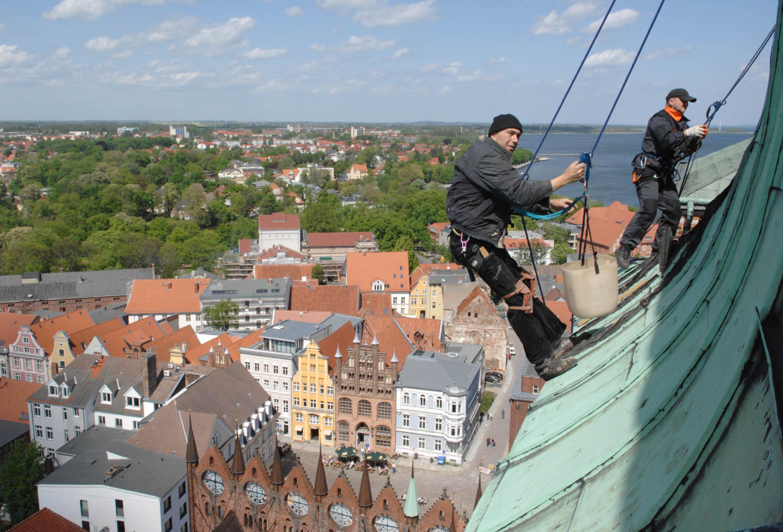 Industriekletterer auf dem Turm der Stralsunder Nikolaikirche. Sie brauchen meist mehrere Tage, um große Fassaden zu inspizieren. Die Drohne soll das in wenigen Stunden schaffen.
