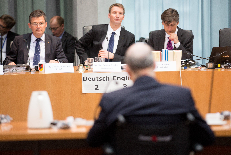 Der Vorsitzende des NSA-Untersuchungsausschusses des deutschen Bundestags, Patrick Sensburg (M, CDU/CSU), eröffnet am 3. Juli 2014 im Elisabeth-Lüders-Haus in Berlin neben Roderich Kiesewetter (CDU) und dem Leiter des Sekretariats des Ausschusses, Harald Georgii (r.) die Sitzung. Derehemalige technische Direktor der NSA, William Binnen (vorne), beschreibt die NSA als totalitäres System.