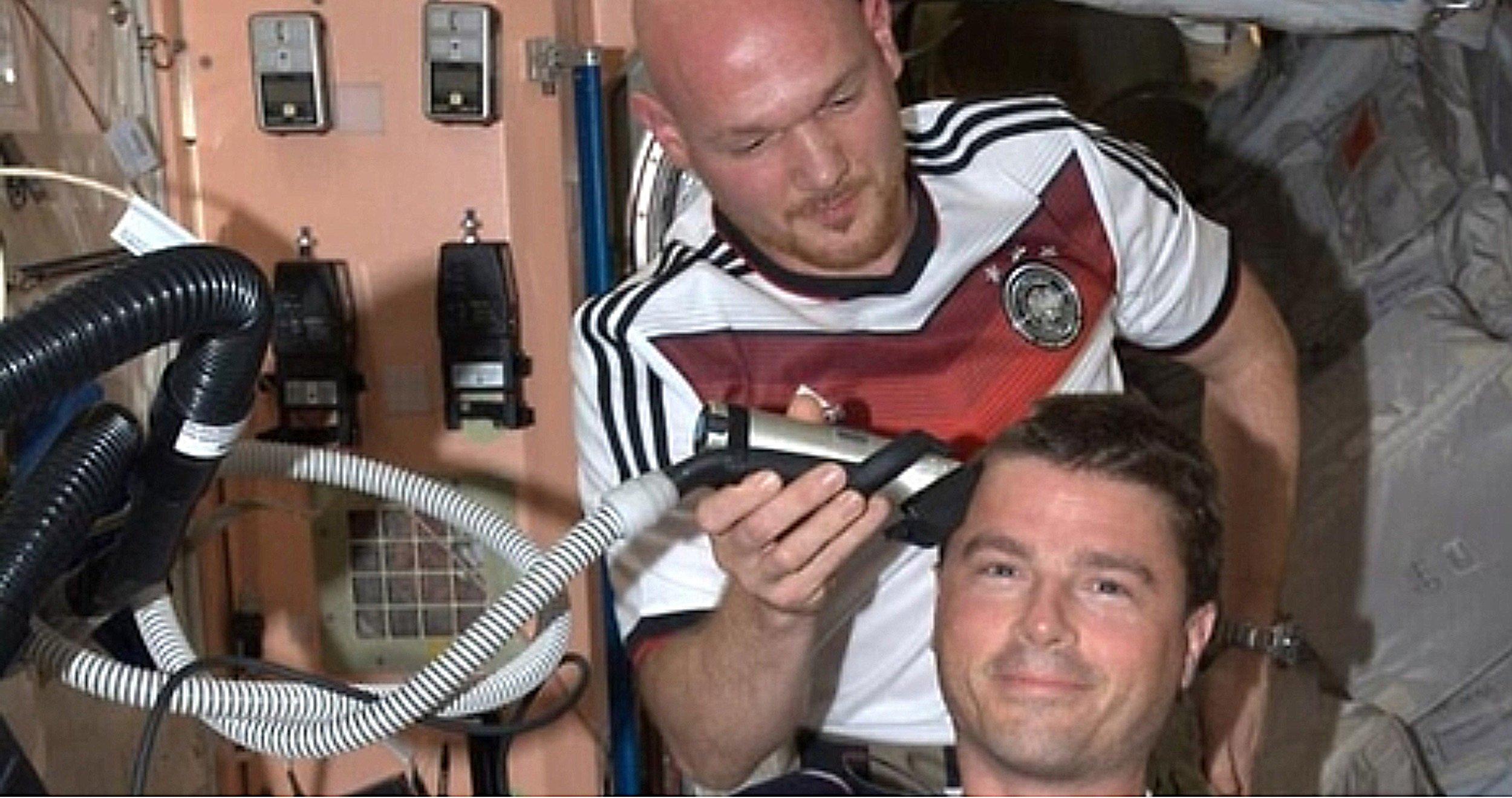 Im Trikot der deutschen Fußball-Nationalmannschaftrasiert Alexander Gerst an Bord der Internationalen Raumstation ISS seinem US-Kollegen Reid Wiseman das Kopfhaar ab. Anlass war eine Wette, nach der sich bei einem WM-Sieg der deutschen Fußballer über die USA die beiden US-Astronauten Wiseman und Swanson eine Glatze verpassen lassen würden. Bei einem Sieg der USA hätte sich Gerst die US-Flagge auf den kahlen Kopf malen lassen.