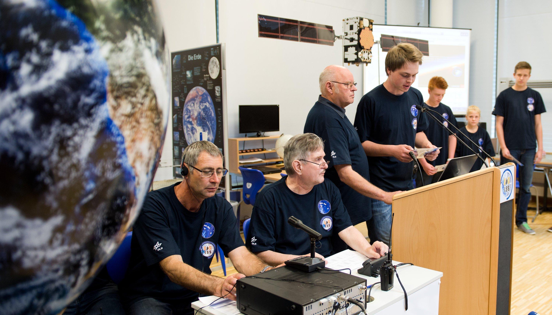 Alexander (17) nimmt zusammen mit Funkamateur Steffen Kröpf (li.), Wolfgang Andree (2.v.l.), Leiter des DLR-Project-Lab, und DLR-Mitarbeiter Ingo Goltz (3.v.l.), mit anderen Schülerinnen und Schülern aus Mecklenburg-Vorpommern am 2. Juli im Deutschen Zentrum für Luft- und Raumfahrt in Neustrelitz per Funk Kontakt mit der Internationalen Raumstation ISS und dem dort arbeitenden deutschen Astronauten Alexander Gerst auf. Während seiner für 166 Tage angesetzten Mission ist Gerst dabei in 100 verschiedene Experimente aller ISS-Partner eingebunden.