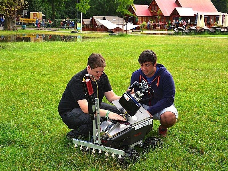 Die Studierenden Michael Schmidpeter (links) und Tim Schuler testen den radgetriebenen Suchroboter Simon auf einer Wiese in Nürnberg.