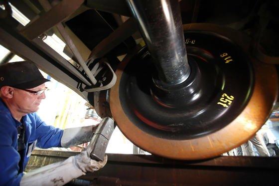 Ein Bahn-Techniker rüstet einen Güterwaggon mit einem neuen Bremsklotz aus Kunststoff aus.Er hat denselben Reibungskoeffizienten wie eine klassische Graugussbremse, raut die Oberfläche des Rades aber nicht auf. Auf der Schiene erzeugt es deshalb die Hälfte weniger Lärm.