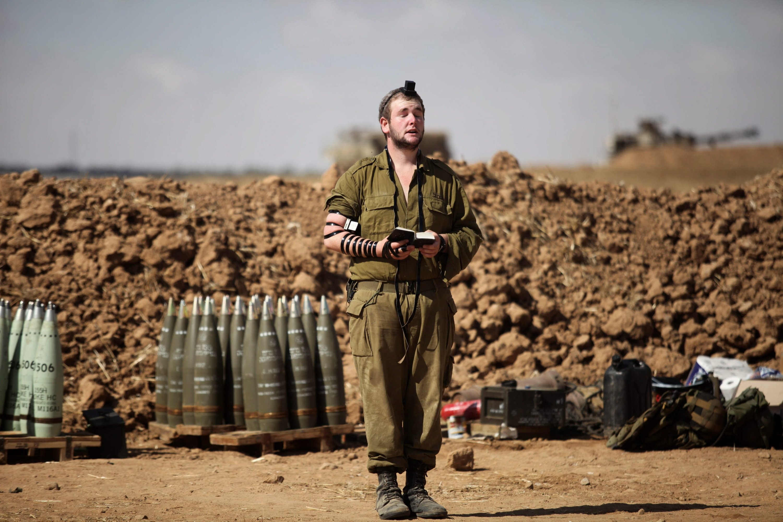 Ein israelischer Soldat vor Artilleriegeschossen.