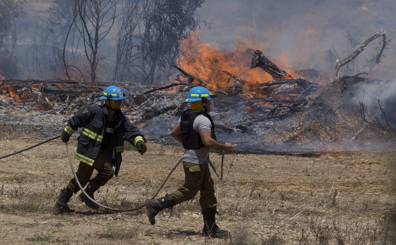 Israelische Feuerwehrmänner wollen am 16. Juli 2014 ein Feuer löschen, dass nach einem Raketenangriff vom Gaza-Streifen auf Ashkelon ausbrach.