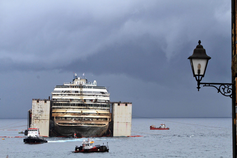 Die von großen Tanks stabilisierte Costa Concordia wird während der Fahrt nach Genua von 14 Schiffen begleitet. Während der Vorbeifahrt an Korsika werden dort die französische UmweltministerinSegoléne Royal und VerteidigungsministerJean-Yves Le Drian die Fahrt beobachten.