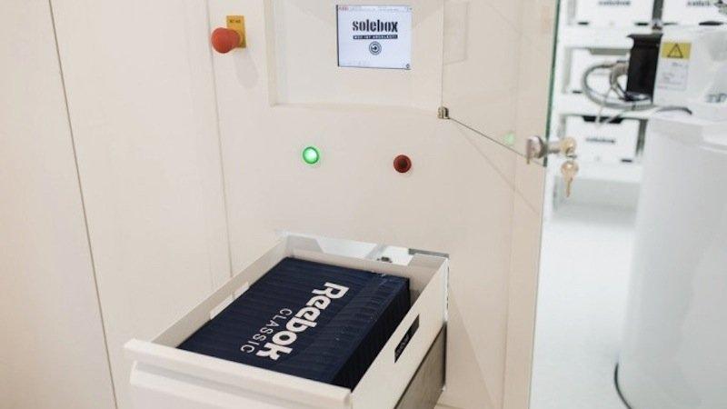 Auf dem Touchscreen gibt der Kunde das Regalfach ein. Der Roboterarm legt die Schuhe dann in eine Durchreiche.