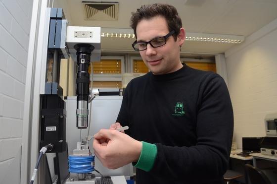 Diplom-Nanowissenschaftler Dennis Holzinger bereitet einen Versuch mit dem neuartigen Analysechip vor, der Krebszellen aufspüren kann. Er platziert ihn auf den Träger eines Elektromagneten, der das magnetische Kraftfeld zur Steuerung der zu untersuchenden Flüssigkeit auf dem Chip aufbaut.