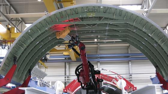 Der Roboterarm kann bis zu elf Meter lange Bauteile inspizieren. In Sekundenschnelle macht der Sensorkopf Bildaufnahmen aller Verbindungspunkte und vergleicht sie mit Soll-Werten in einer Datenbank.