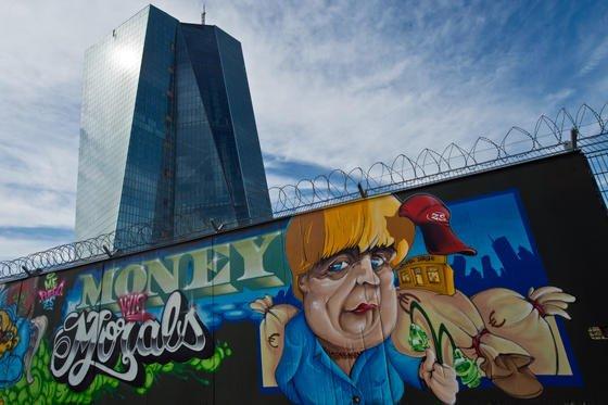 """""""Money kills Moral"""" (""""Geld tötet die Moral"""") lautet die Botschaft eines Graffitis am Zaun der Europäischen Zentralbank (EZB) in Frankfurt neben einer Karikatur von Bundeskanzlerin Angela Merkel. Jetzt haben Hacker eine Datenbank der EZB geknackt, 20.000 Adressen gestohlen und versucht, von der EZB ein Lösegeld zu erpressen."""