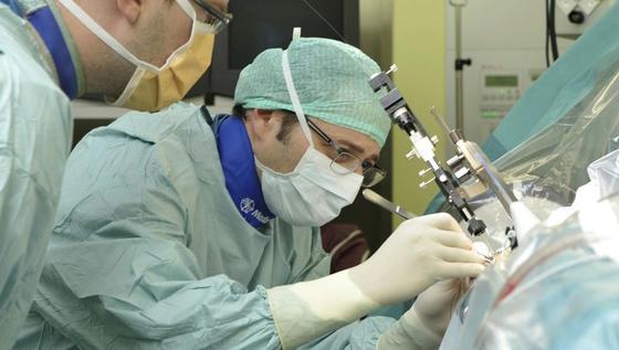 Claudio Pollo vom Inselspital in Bern setzt einem Patienten eine Minisonde für die Tiefe Hirnstimulation (THS) ein. Die verbesserte Elektrode schaltet das lästige Zittern ab, unter dem Parkinson-Patienten leiden.