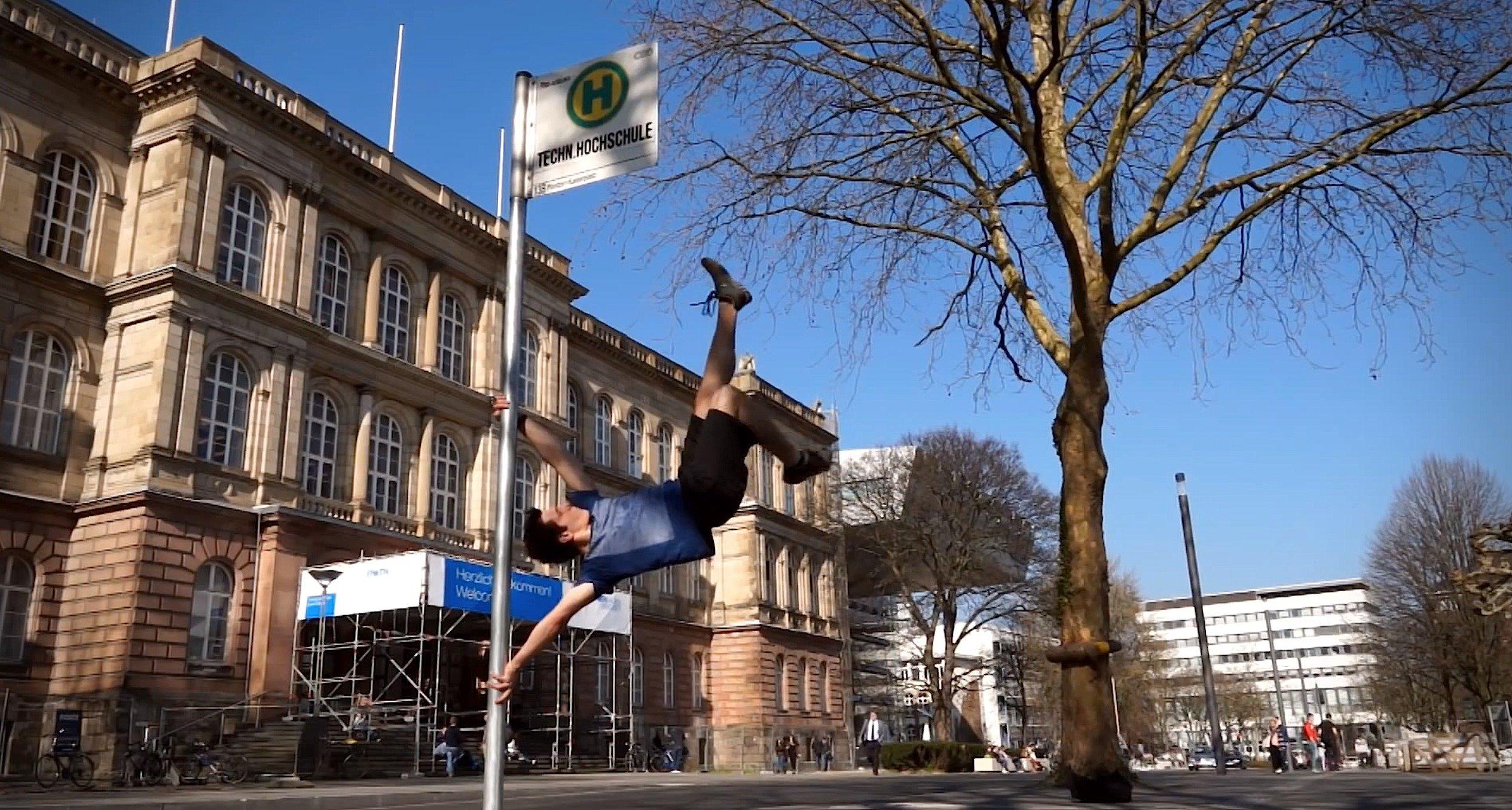 Viel Kraft in den Armen: Ingenieurstudent der RWTH Aachen hängt am Haltestellenschild der Uni.