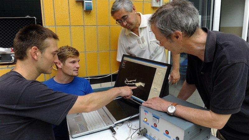 Der Jenaer Sportwissenschaftler Dr.Stefan Hochstein zeigt seinen Kollegen am Computer die Visualisierung der Strömung, die den Schwimmer umgibt.