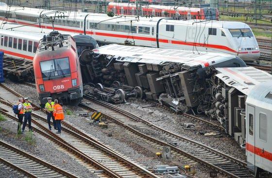 Polizeibeamte stehen in Mannheim am Hauptbahnhof vor umgekippten Waggons des Eurocitys und der Lok des Güterzugs. Derzeit prüfen Ermittler unter anderem, ob eine falsch gestellte Weiche die Unfallursache war.