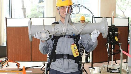 Am Rücken des Arbeiters befindet sich ein Bügel als Teil des Exoskeletts: An diesem lassen sich Bauteile befestigen. Das Gehen ist nahezu mühelos, da das Exoskelett die Muskelkraft des Trägers verstärkt.