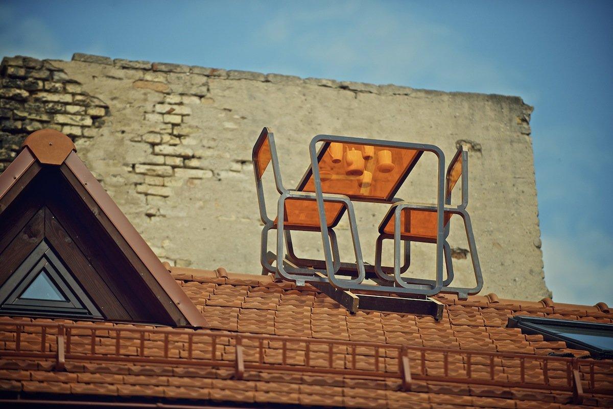 DieTisch- und Stuhlkombination der Designerin Ainė Bunikytė ist auf einer Unterkonstruktion aus Metall befestigt, die flächig auf dem Dach liegt.