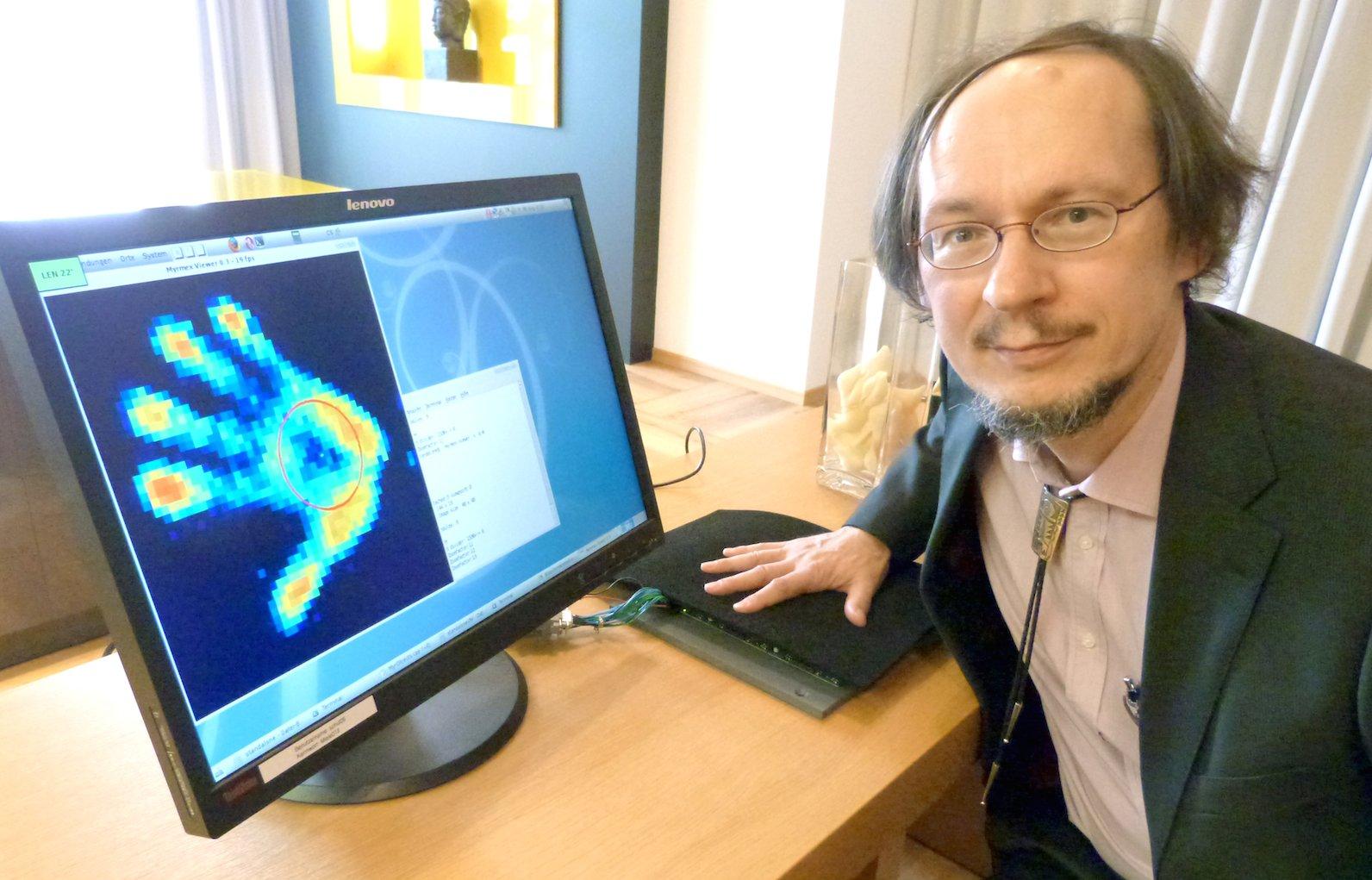 """Forscherinnen und Forscher befassen sich in dem Projekt auch mit Sensortechnik. Prof. Dr. Helge Ritter demonstriert """"Myrmex"""". Der Forschungsprototyp erkennt den unterschiedlichen Druck, den Objekte ausüben, die darauf platziert werden."""